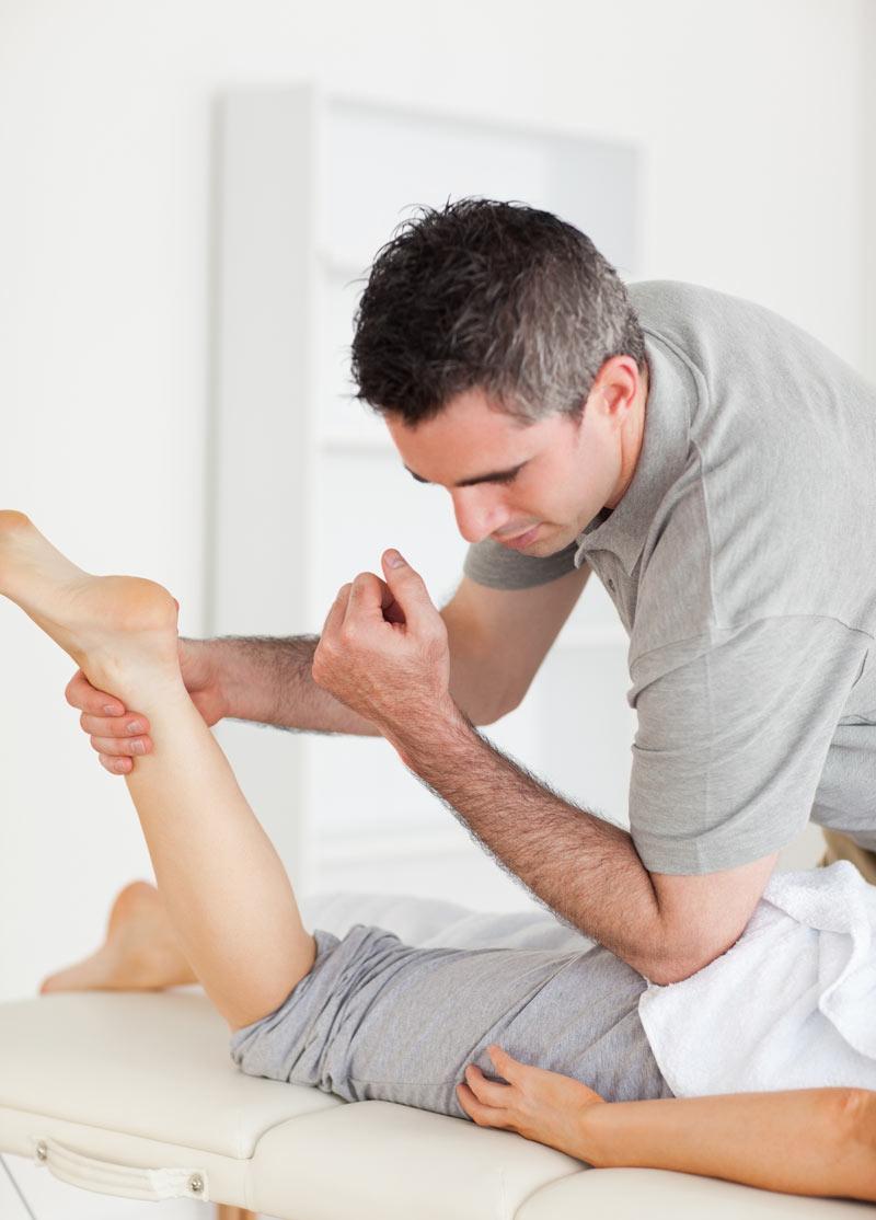 osteopath-stretches-female-customer-leg