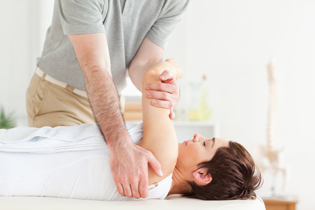 osteopath stretching womans arm
