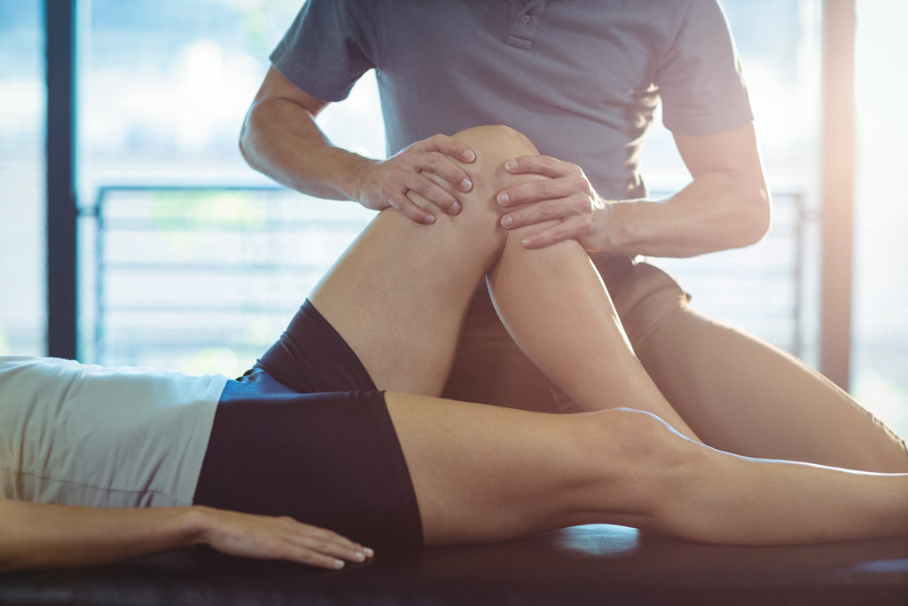 osteopath giving knee therapy